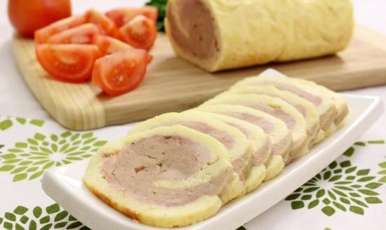 рулет из сыра с фаршем на белом блюде