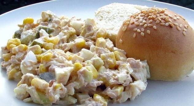 салат с тунцом, рисом и кукурузой на тарелке с булочкой